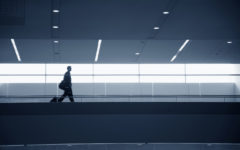 Businessman walking in airport with baggage, side view